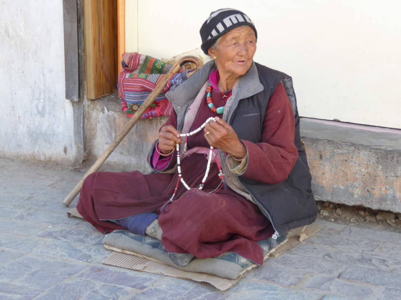 Tibetan woman sells necklaces