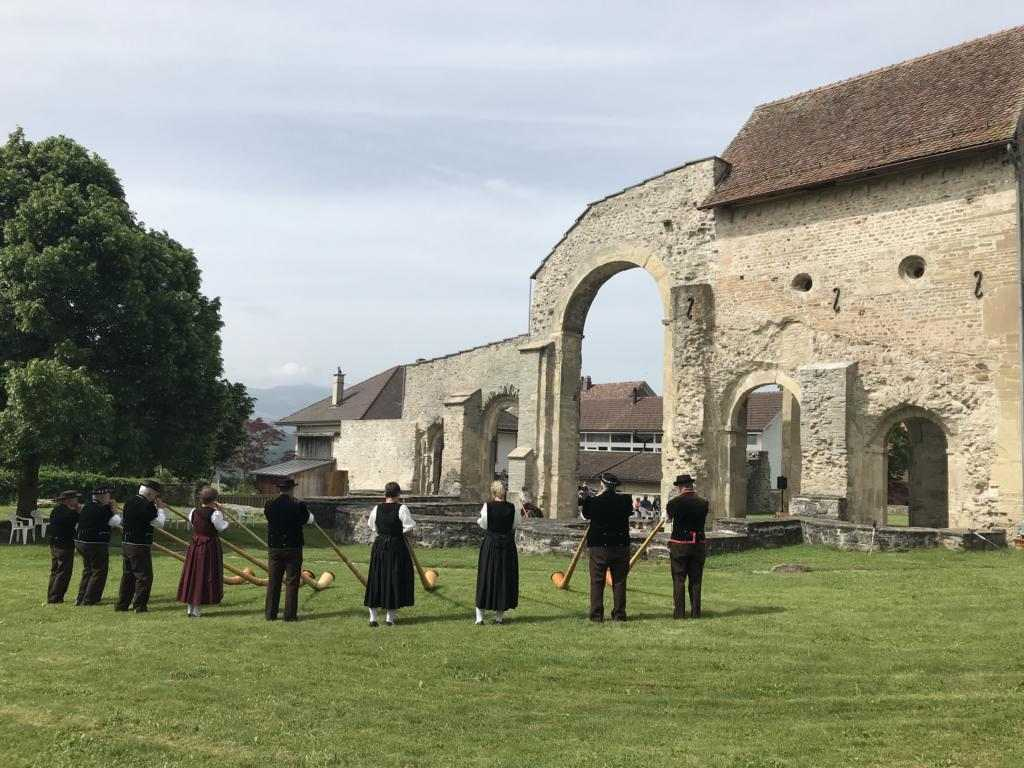 Group playing Alphorn behind the ruins